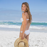 Beautiful happy blonde on the beach in white bikini holding sunhat