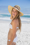 Beautiful happy blonde on the beach in white bikini and sunhat