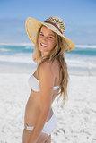 Beautiful happy blonde on the beach in white bikini and sunhat