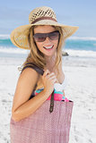 Beautiful laughing blonde on the beach holding bag