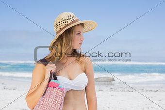 Beautiful blonde on the beach holding bag