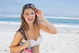 Beautiful smiling blonde on the beach holding bag