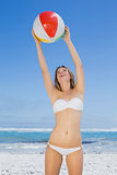 Smiling slim woman catching beach ball