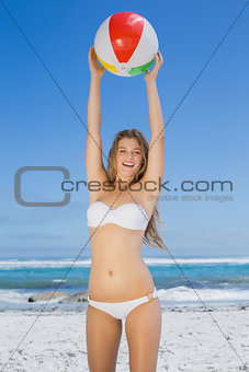 Smiling slim woman catching beach ball