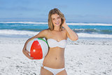Smiling slim woman holding beach ball