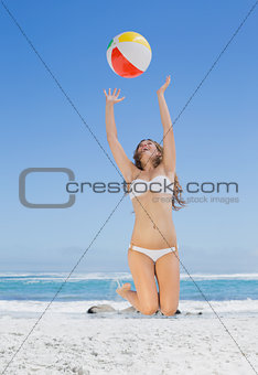 Fit blonde in white bikini throwing beach ball