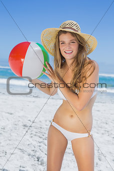 Fit blonde in white bikini and straw hat holding beach ball