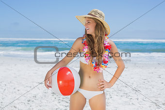 Fit smiling blonde in white bikini and straw hat holding beach ball