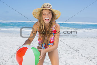 Fit laughing blonde in white bikini and straw hat holding beach ball