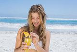 Pretty blonde in white bikini holding cocktail on the beach