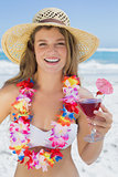 Pretty smiling blonde in floral garland holding cocktail on the beach