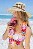 Pretty blonde in floral garland sipping cocktail on the beach