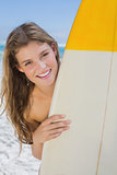 Pretty surfer girl holding her surfboard on the beach