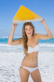 Smiling surfer girl holding her surfboard on the beach