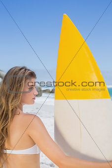 Fit surfer girl holding her surfboard on the beach