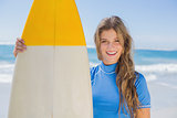 Fit smiling surfer girl on the beach with her surfboard
