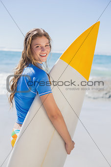 Fit happy surfer girl on the beach with her surfboard