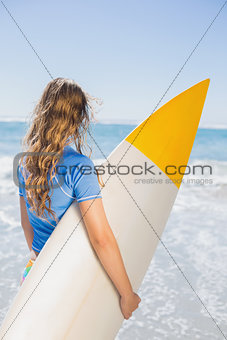 Fit surfer girl on the beach with her surfboard