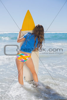 Fit surfer girl standing on the beach with her surfboard