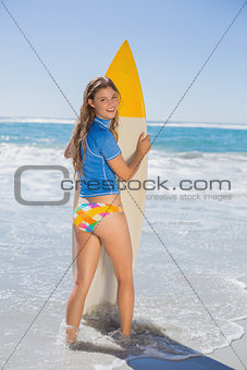 Fit smiling surfer girl standing on the beach with her surfboard