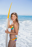Beautiful smiling surfer girl standing on the beach with her surfboard