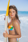 Beautiful surfer girl standing on the beach with her surfboard