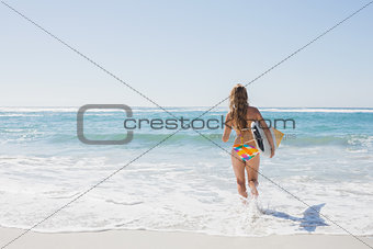Beautiful surfer girl walking to the sea with her surfboard