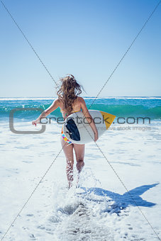 Fit surfer girl running to the sea with her surfboard