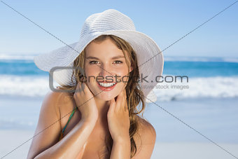 Beautiful girl in white straw hat smiling at camera on beach