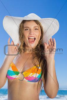 Beautiful girl in bikini and straw hat looking at camera on beach