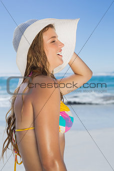 Beautiful girl in bikini and straw hat smiling on beach