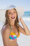 Beautiful girl in bikini and straw hat smiling at camera on beach