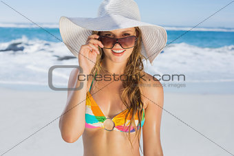 Beautiful girl in bikini and straw hat smiling at camera on beach