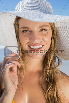Beautiful girl in bikini and straw hat on the beach smiling at camera