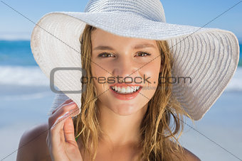 Beautiful girl in straw hat on the beach smiling at camera