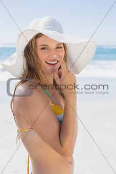 Beautiful girl putting spf on nose on the beach smiling at camera