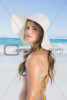 Beautiful girl on the beach posing in white straw hat and bikini