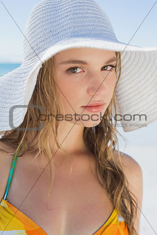 Beautiful girl on the beach smiling in white straw hat and bikini