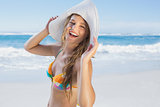 Beautiful girl on the beach laughing in white straw hat and bikini
