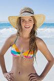 Beautiful girl on the beach smiling in white straw hat and bikini