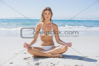 Beautiful girl in white bikini sitting in lotus pose on beach