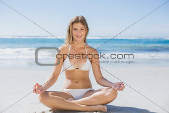 Beautiful girl in white bikini sitting in lotus pose on beach
