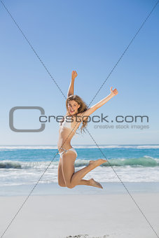 Fit smiling woman in white bikini leaping on beach