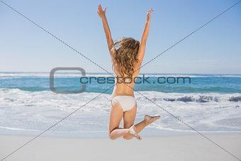 Fit woman in white bikini leaping on beach