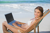 Smiling woman relaxing in deck chair on the beach using laptop