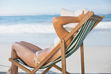 Slim woman relaxing in deck chair on the beach