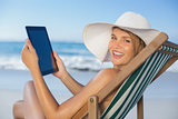 Smiling woman relaxing in deck chair on the beach using tablet