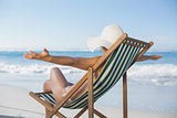 Woman relaxing in deck chair with arms outstretched