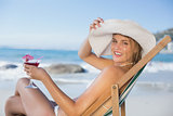 Smiling woman relaxing in deck chair with cocktail