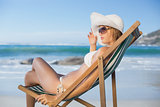 Pretty woman relaxing in deck chair on the beach